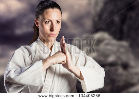 Female fighter performing hand salute against rock crashing down from cliff