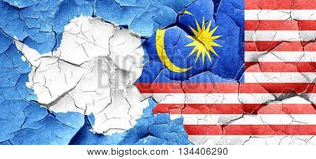 antarctica flag with Malaysia flag on a grunge cracked wall