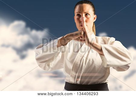 Female fighter performing hand salute against night sky