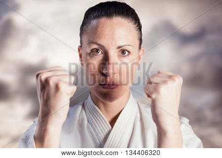 Female fighter performing karate stance against blue sky with white clouds