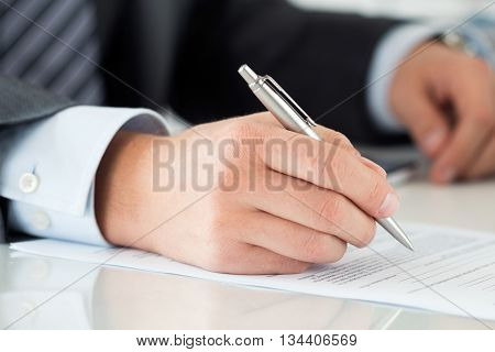 Close up of businessman hands signing documents. Man writing something sitting at his office. Partnership agreement of contact signing closing balance or making financial report concept
