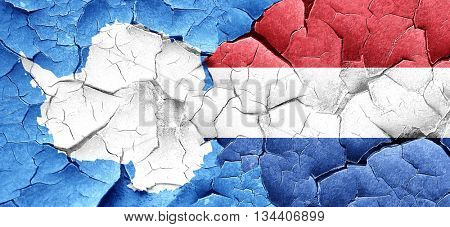 antarctica flag with Netherlands flag on a grunge cracked wall