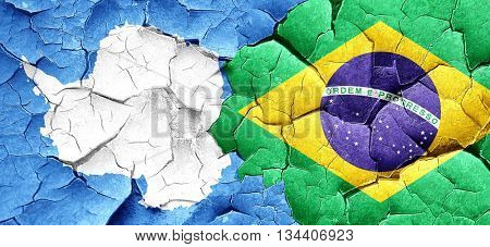 antarctica flag with Brazil flag on a grunge cracked wall