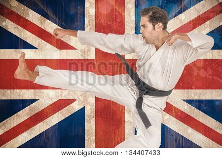 Fighter performing karate stance against union jack flag in grunge effect