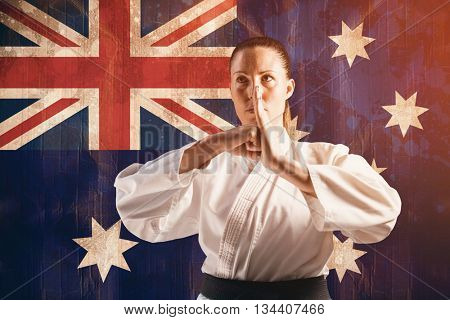 Female fighter performing hand salute against australia flag in grunge effect