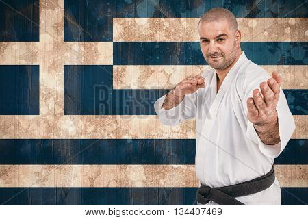 Fighter performing karate stance against greece flag in grunge effect