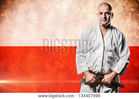 Fighter tightening karate belt against digitally generated image of polish flag