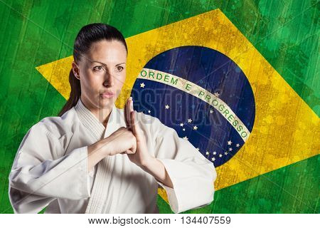 Female fighter performing hand salute against brazil flag in grunge effect