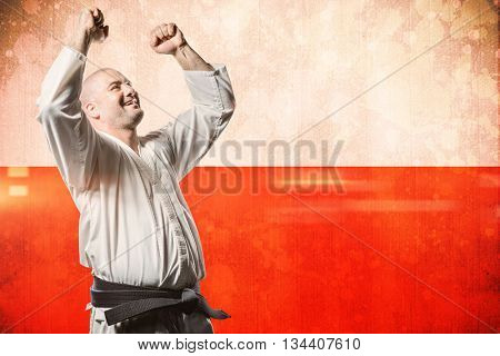 Fighter posing after victory against digitally generated image of polish flag