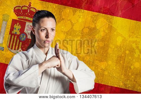 Female fighter performing hand salute against spain flag in grunge effect