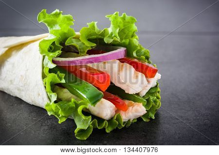 Mexican fajita with chicken, peppers, onion and lettuce on slate background