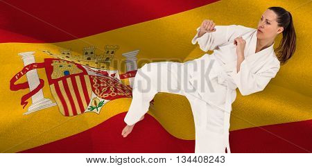 Fighter performing karate stance against digitally generated spain national flag