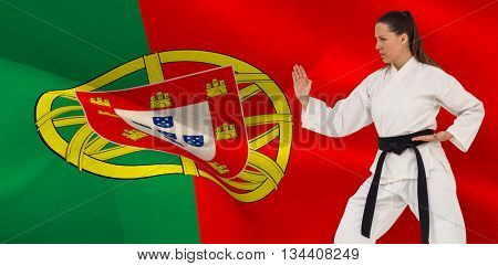 Female fighter performing karate stance against digitally generated portugal national flag