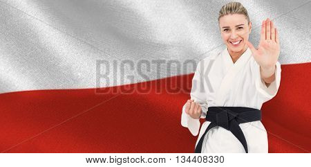 Female athlete practicing judo against digitally generated polish flag rippling