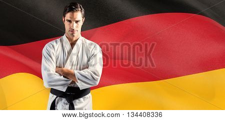 Portrait of fighter standing on black background against digitally generated german national flag