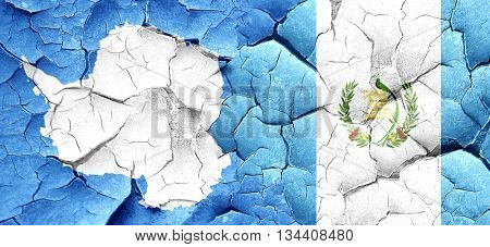 antarctica flag with Guatemala flag on a grunge cracked wall
