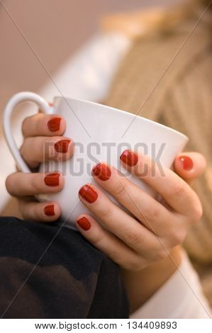 Young woman's hands with red nail polish holding a white cup. A cup of coffe. A blond woman with a cup of tea and beige scarf
