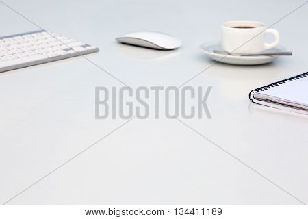 Bright Open Space Office White Table with Coffee Mug Opened Blank Notepad and Computer Keyboard Mouse on Desk Side View with Reflections and Copy Space