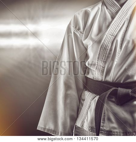 Mid section of karate player against spotlight