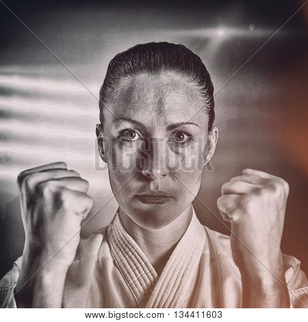 Female fighter performing karate stance against spotlight
