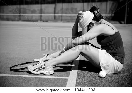 Upset tennis player sitting on court on a sunny day