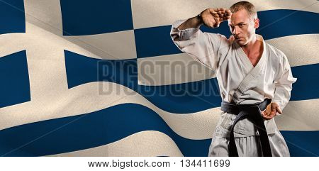 Fighter performing karate stance against digitally generated greek national flag