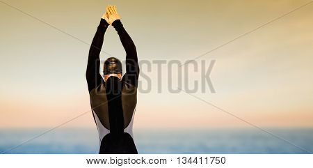 Rear view of swimmer in wetsuit while diving against beautiful sunset on a sunny day