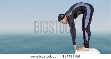 Swimmer in wetsuit preparing to dive against scenic view of sea against sky