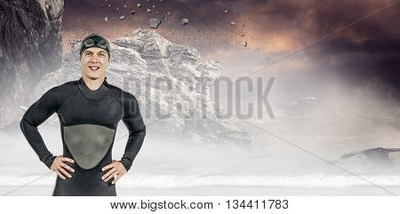 Portrait of confident swimmer in wetsuit against rock crashing down from cliff