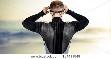 Rear view of swimmer in wetsuit wearing swimming goggles against surf board standing on the sand