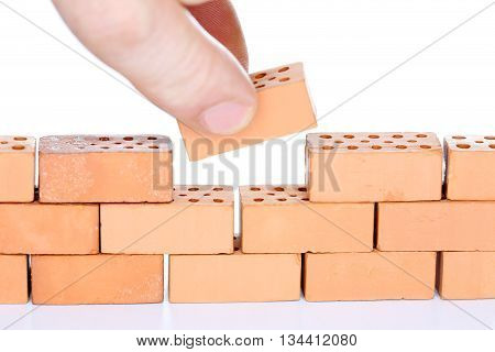 man inserts the last brick in a wall