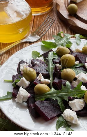 Beet (beetroot) salad with cheese olives and arugula on the white plate. Olive oil and lemon dressing. On the wooden table.