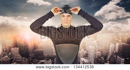 Swimmer in wetsuit wearing swimming goggles against aerial view of a city on a cloudy day