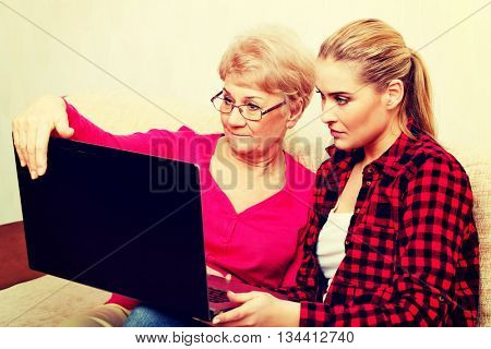 Mother and daughter sitting on couch and watching something on laptop