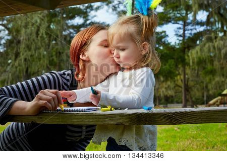 Mother kissing daughter drawing colors in a park lake
