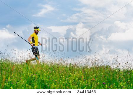 Young Man Runs Down In The Green Grass While Practicing Nordic Walking
