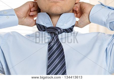 Handsome businessman preparing to official event straighten tie. New job interview self motivation for confidence trying fashionable necktie knot tailor service concept
