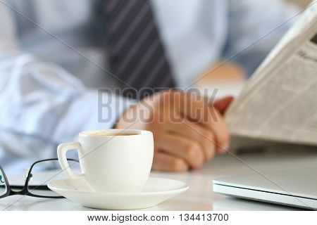 Cup of morning coffee on worktable with business analyst hold in hands and read newspaper on background. Price quotation on the exchange relaxing at workplace or football match result concept