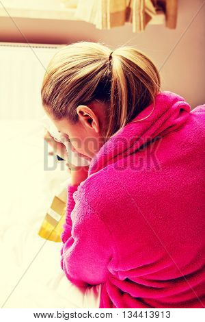 Young woman sitting on the bed crying and drinking whiskey