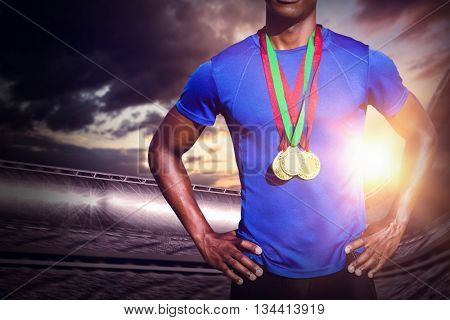 Portrait of athletic man chest holding gold medals against composite image of stadium
