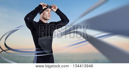 Swimmer in wetsuit wearing swimming goggles against beautiful sunset on a sunny day