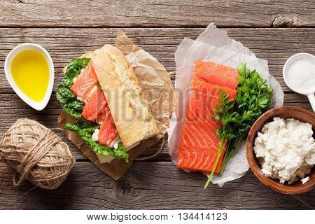 Sandwich with ciabatta bread, salmon and romaine salad on wooden table. Top view