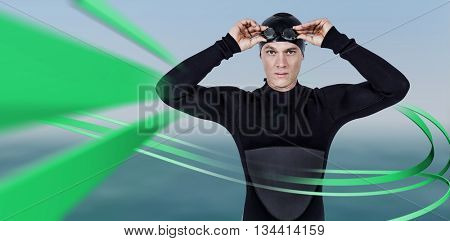 Swimmer in wetsuit wearing swimming goggles against sunset of a beautiful day