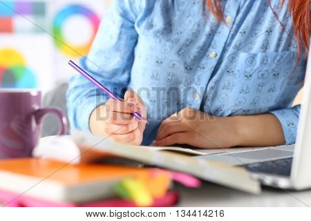 Female student blogger or designer at workplace holding pencil and writing or making sketches. Woman writing letter list plan making notes doing homework. Education or creative work concept