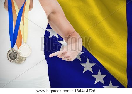 Female athlete pointing her medals against digitally generated bosnian flag