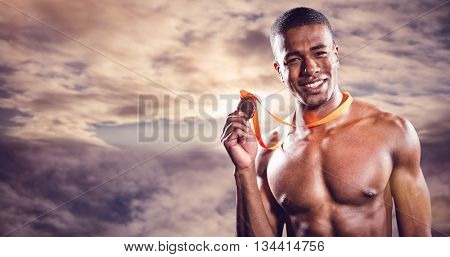 Fighter holding gold medal against cloudy sky