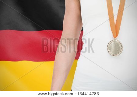 Female athlete wearing a medal against digitally generated german national flag