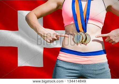 Close up of sportswoman chest with medals against digitally generated swiss national flag