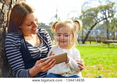mother and daughter playing with smartphone together sitting in the park tree