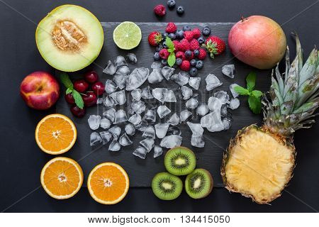 Rectangle of pineapple mango kiwi oranges lime melon nectarine and cherries strawberries blueberries raspberries in center ice cubes on black background. Fruits berries rectangle. Horizontal.